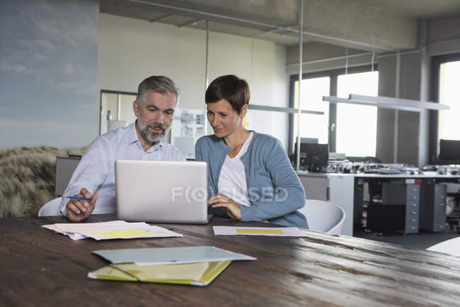 Businessman and businesswoman using laptop in office — Stock Photo