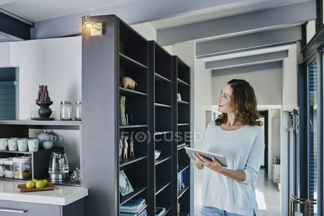 Woman regulating lamp with digital tablet — Stock Photo