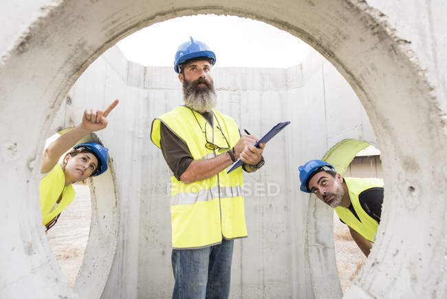 Industrial workers examining concrete structures — Stock Photo