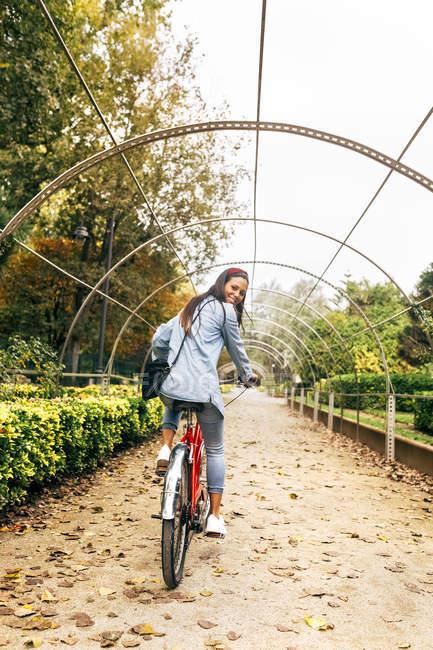 Junge frau mit fahrrad im park — Stockfoto