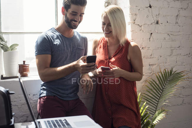 Smiling young man and woman with cell phones in a loft — Stock Photo