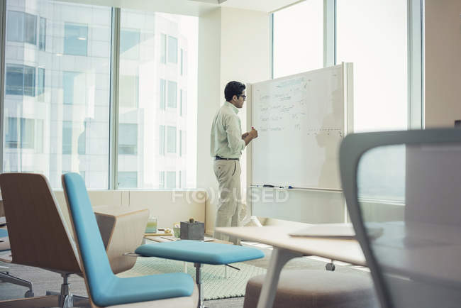 Businessman writing on whiteboard in modern office — Stock Photo
