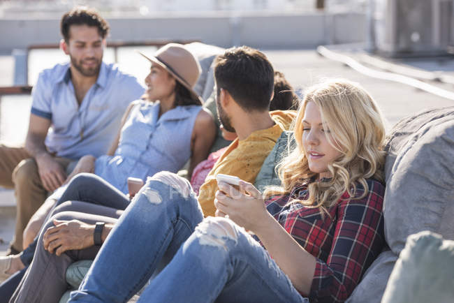 Friends on couch at rooftop party — Stock Photo