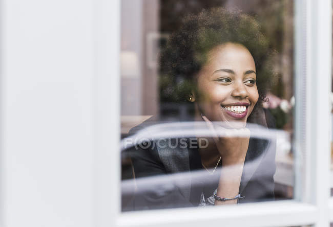Smiling young woman looking out of window — Stock Photo