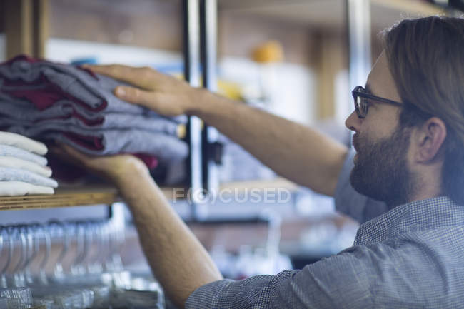 Bearded male salesperson putting clothes in store — Stock Photo