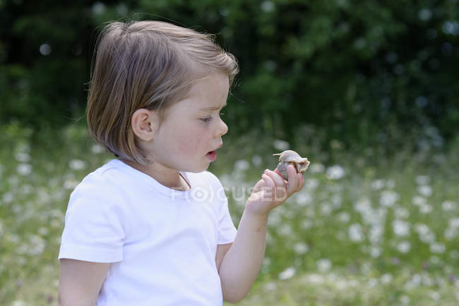 Little girl watching snake holding in hand — Stock Photo