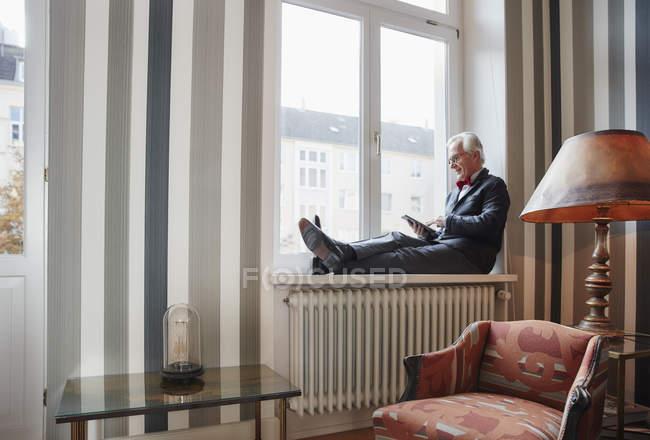 Senior man sitting in windowsill using tablet — Stock Photo