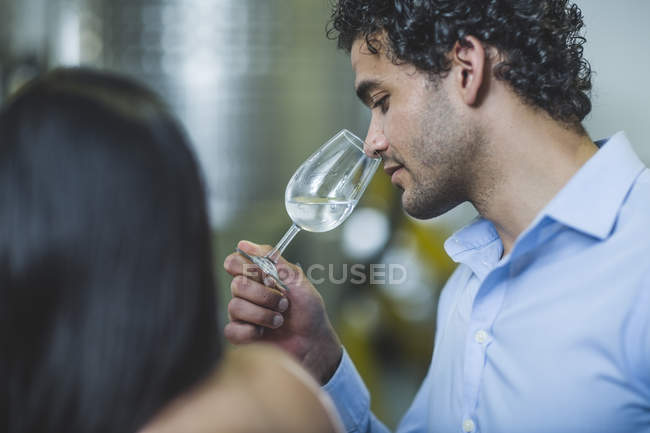 Young man smelling gin at tasting in distillery — Stock Photo