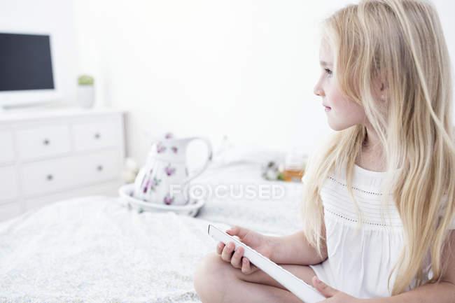 Ragazza seduta sul letto e utilizzando il telecomando — Foto stock