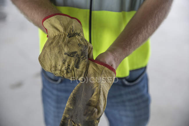 Construction worker putting on protective gloves — Stock Photo