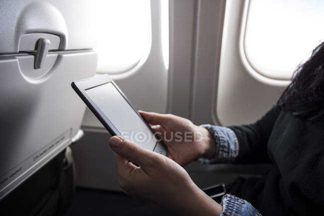 Woman sitting in airplane using E-Book, partial view — Stock Photo