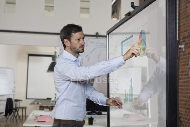 Businessman handling graphs on screen in office — Stock Photo