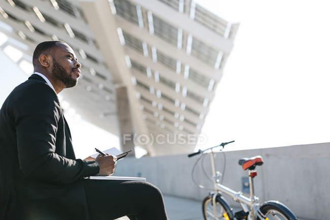 Homme d'affaires assis sur les escaliers avec ordinateur portable — Photo de stock