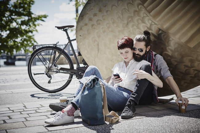 Портрет подружжя за допомогою мобільного телефону біля скульптури — стокове фото