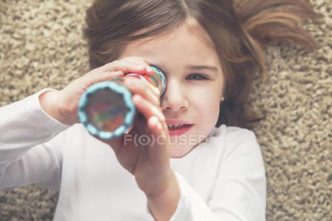 Маленькая девочка с калейдоскопом лежит на ковре — стоковое фото