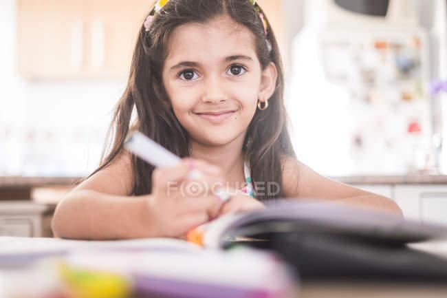 Portrait of smiling brunette girl doing homework — Stock Photo