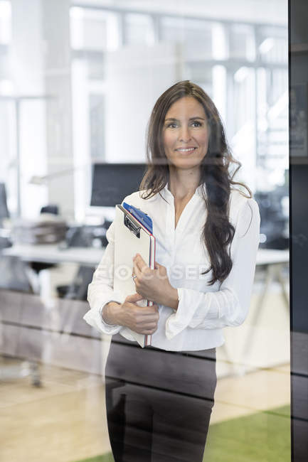 Portrait of confident businesswoman in office holding clipboard — Stock Photo