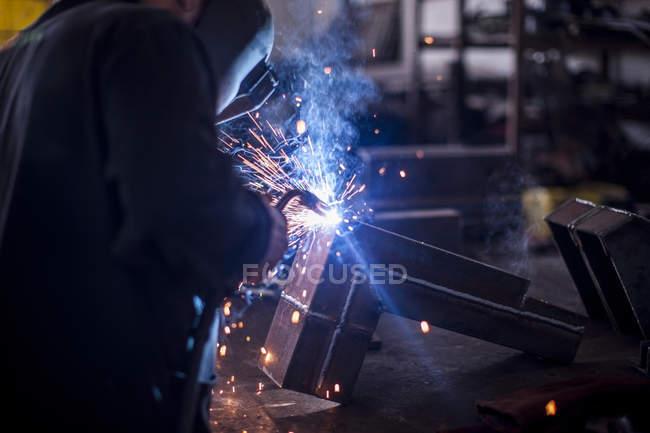 Primer plano del soldador en la máscara de soldadura en el trabajo en el taller - foto de stock
