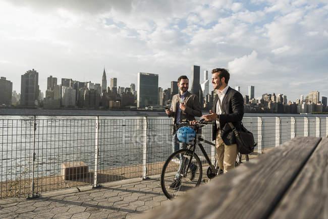 Due uomini d'affari con bicicletta passeggiando lungo East River, New York, USA — Foto stock