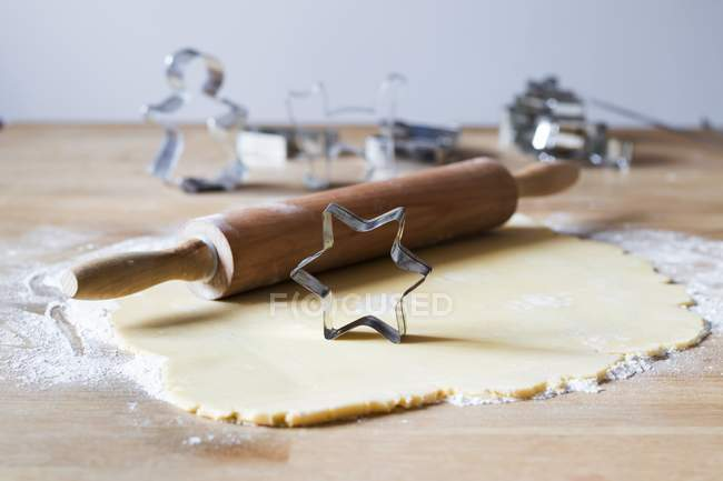 Closeup view of rolled dough with rolling pin and star-shaped cookie cutter on flour — Stock Photo