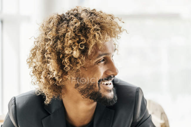 Portrait of a laughing young businessman looking sideways — Stock Photo