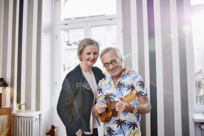 Счастливая старшая пара с мужчиной в гавайской рубашке, играющим на укулеле — стоковое фото