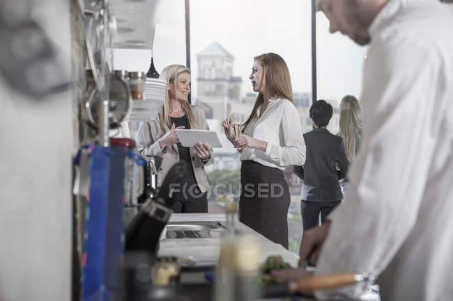 Two women with tablet talking in a restaurant — Stock Photo