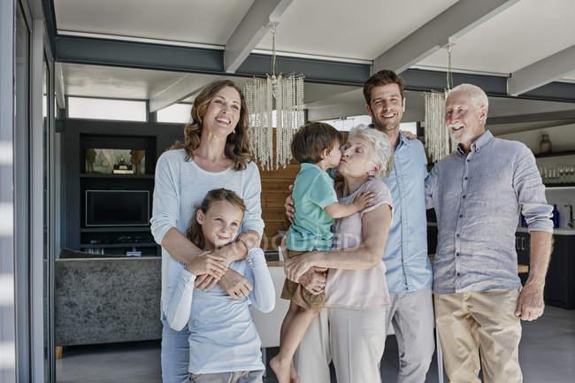 Retrato de sonriente familia de tres generaciones en el interior - foto de stock