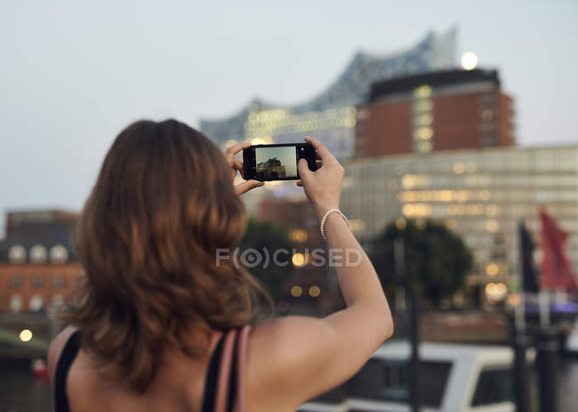 Germany, Young woman in Hamburg taking pictures with her smart phone — Stock Photo