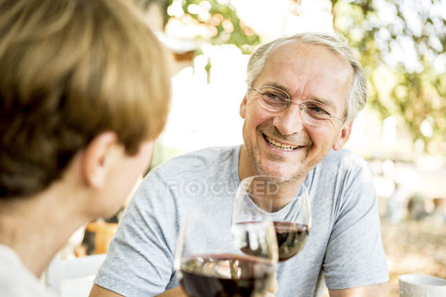 Glückliches Seniorenpaar bei einem Glas Rotwein im Freien — Stockfoto