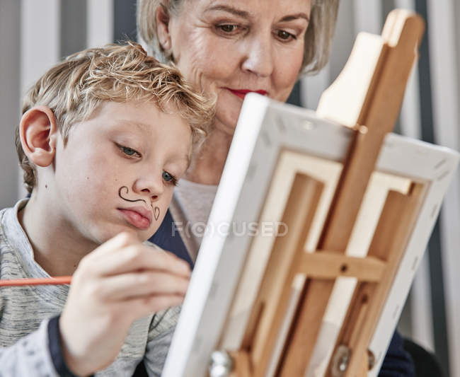Grandmother and grandson with Dali moustache at easel — Stock Photo