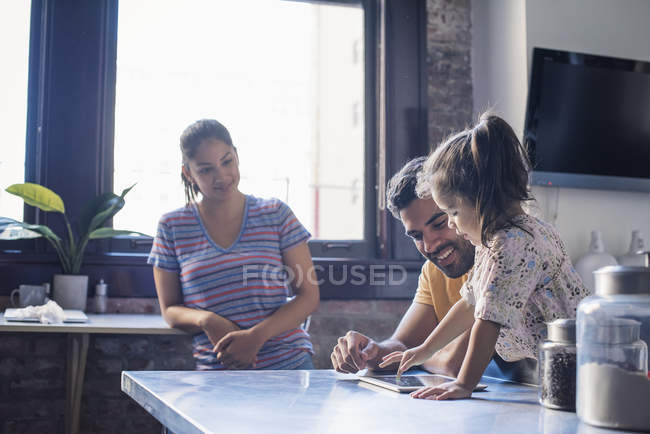 Family in domestic kitchen, father and daughter reading book together — Stock Photo