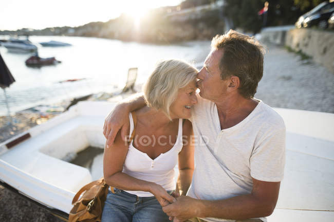 Senior couple sitting on edge of a boat on the beach at evening twilight — Stock Photo