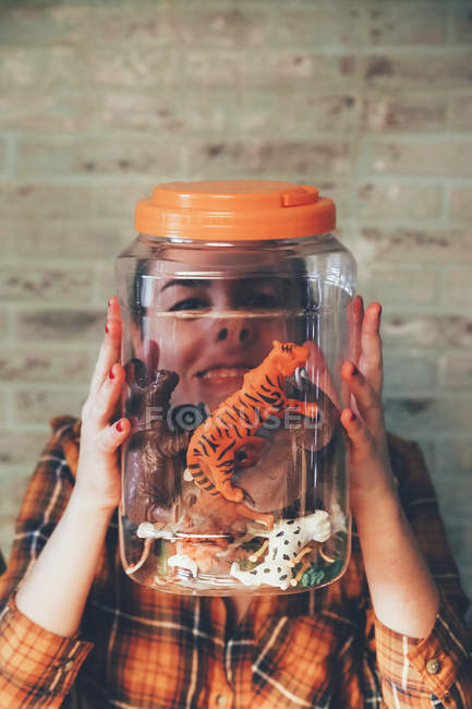 Funny woman pressing her face against jar with plastic animals — Stock Photo