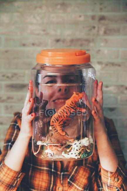 Смешная женщина, нажав ее лицо против банку с пластиковых животных — стоковое фото