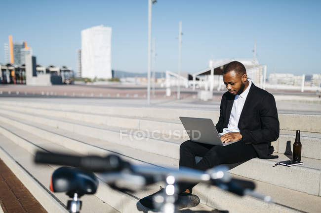 Businessman sitting on stairs with bottle of beer — Stock Photo