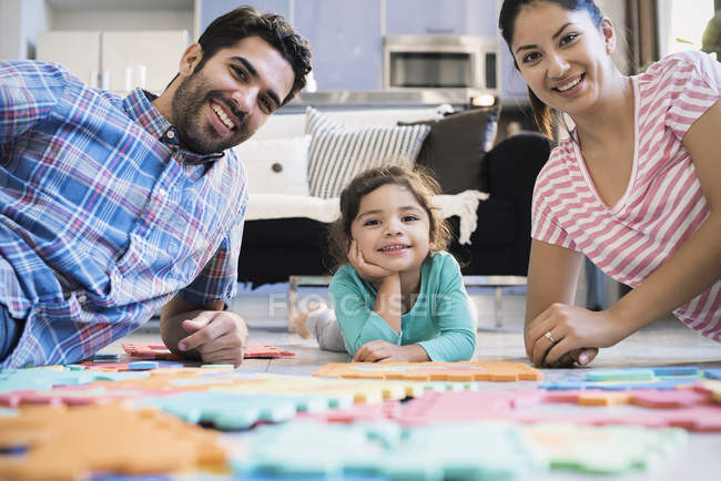 Happy family lying on floor with puzzles smiling at camera — Stock Photo