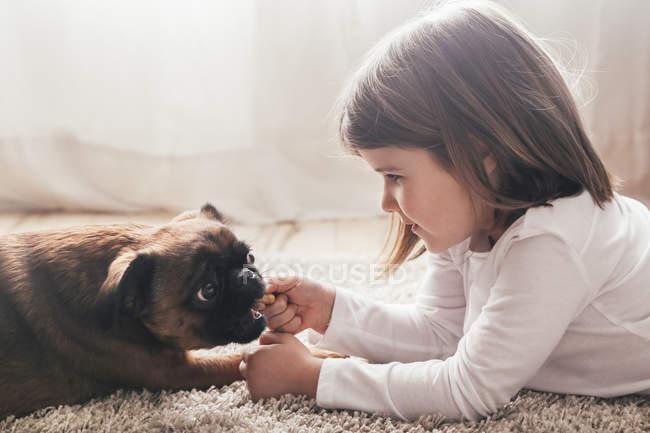 Bambina sdraiata sul tappeto con cane a casa — Foto stock