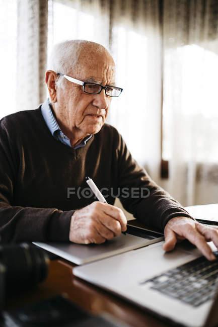 Fotógrafo sênior, trabalhando com seu computador em casa — Fotografia de Stock