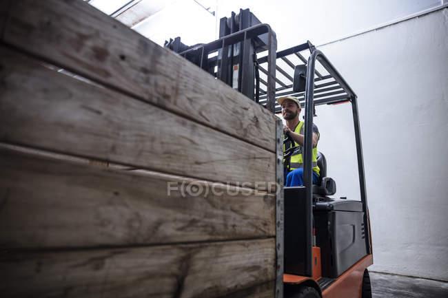 Männliche Handeling Gabelstapler Maschine tragen Schutzausrüstung und Overalls in Lager — Stockfoto