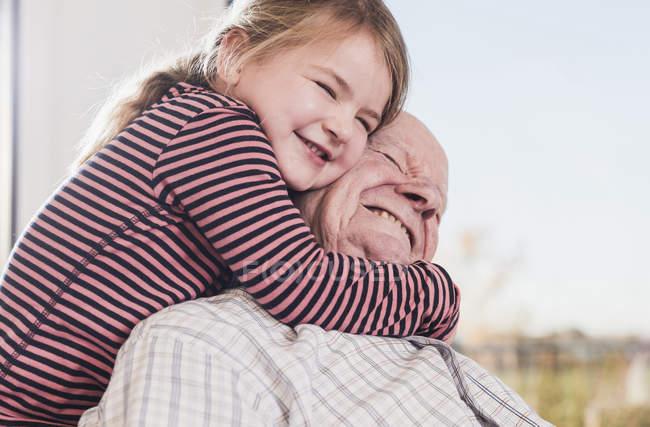 Primer plano de la nieta abrazando abuelo delante de la ventana - foto de stock