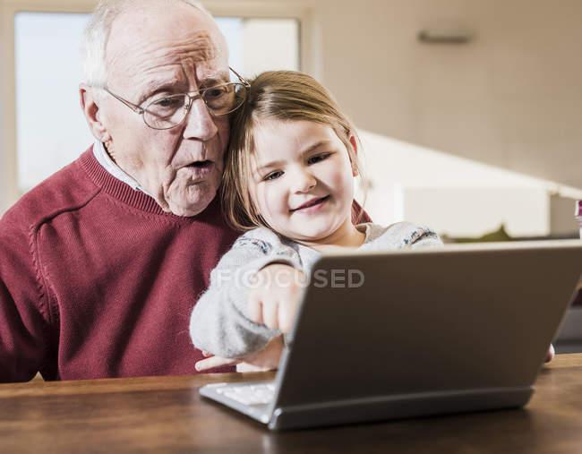 Abuelo y nieta usando laptop juntos - foto de stock