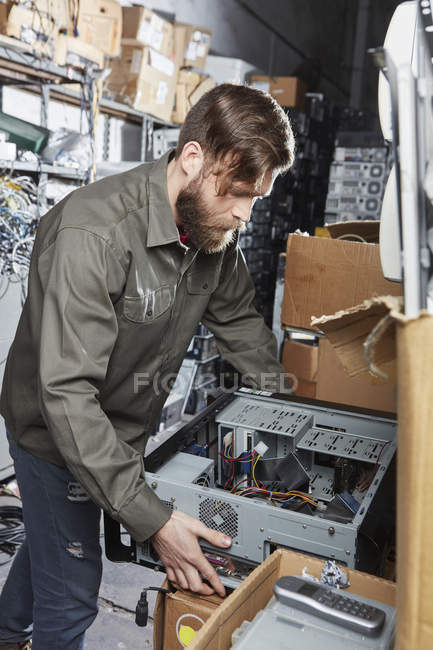 Worker carrying pc casing in computer recycling plant — Stock Photo