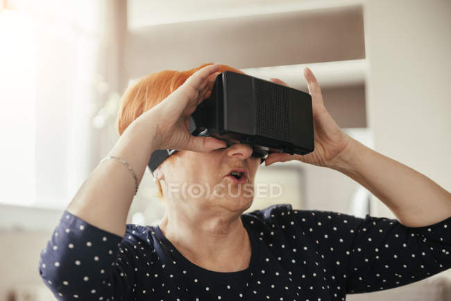 Amazed mature woman in cyber glasses — Stock Photo