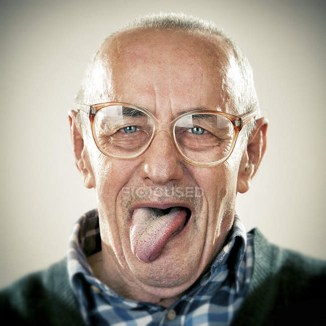Portrait of senior man pulling face and looking at camera — Stock Photo