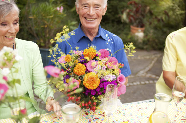 Seniors celebrating birthday oarty in garden — Stock Photo