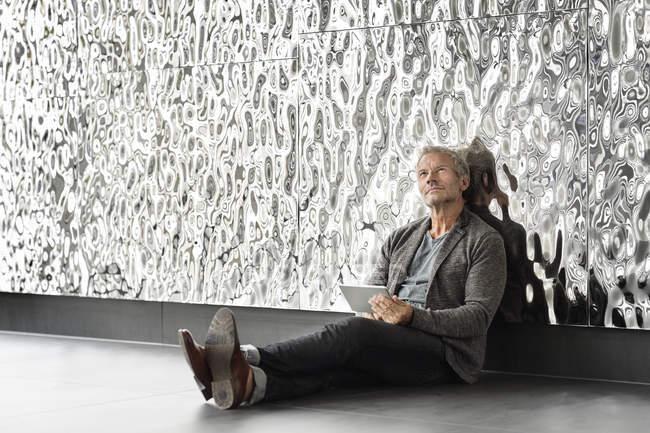 Бізнесмен, сидячи біля rippled стіни з планшетного ПК, шукаючи — стокове фото