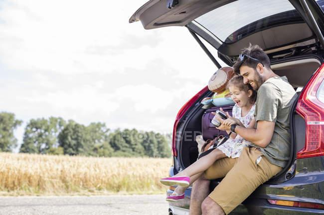 Vater und Tochter sitzen im offenen Kofferraum und schauen in die Kamera — Stockfoto