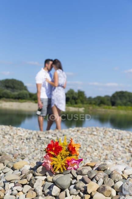 Bouquet de fleurs sur les cailloux de rivière, romantique couple debout sur le fond — Photo de stock