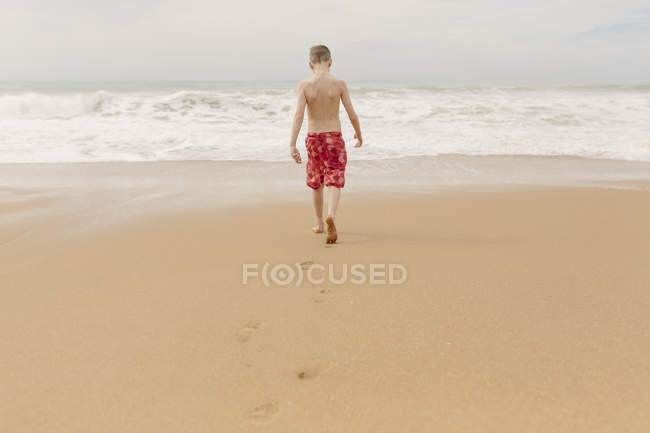 Boy walking on the beach — Stock Photo